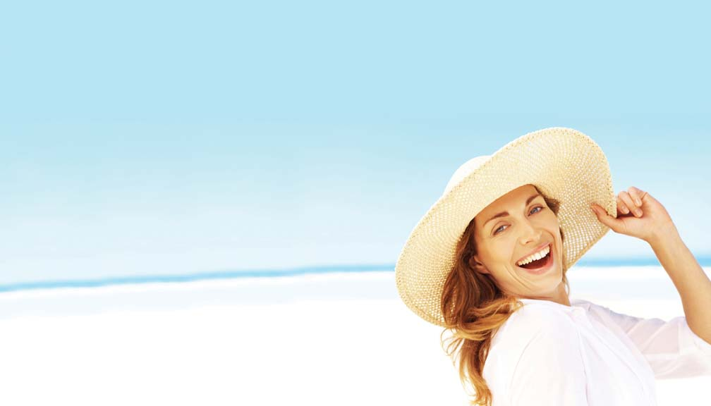 A smiling woman on a beach holding onto the rim of her sun hat - copyspace